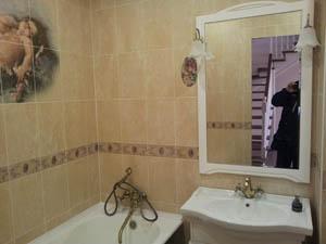 В санузле уложена плитка, установлены: ванна, раковина и зеркало.