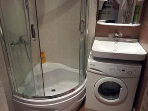 В маленький санузел поместили душевую кабину, стиральную машину под раковину
