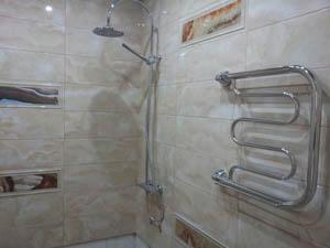 Стены ванной красиво выложили плиткой, установили душ, сушку и батарею